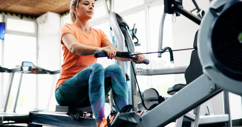 Trening kobiety przecinający szkolenie ćwiczy cardio używa wioślarską maszynę fotografia royalty free