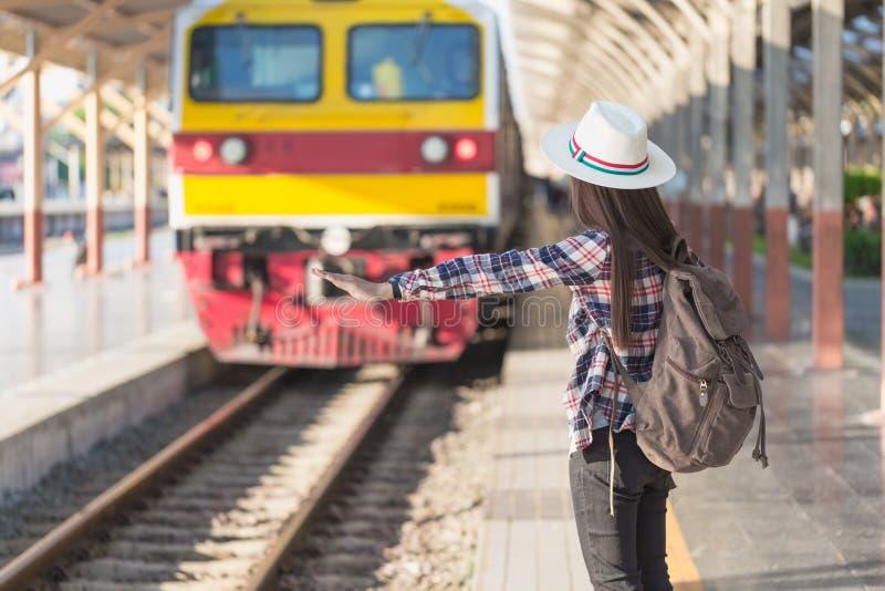 Treno aspettante della bella giovane donna asiatica alla stazione ferroviaria, fotografia stock libera da diritti