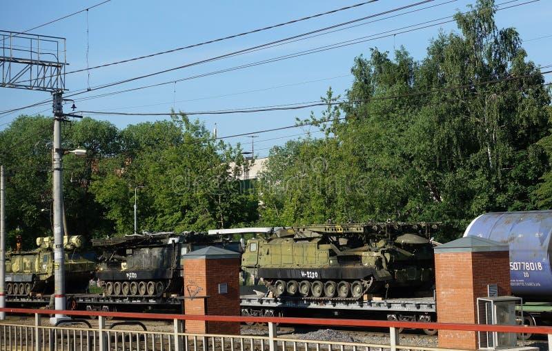Treno del carico che porta attrezzature militari ed i carri armati muniti militari su un binario del trasporto fotografie stock