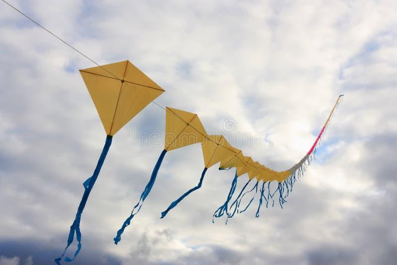 Treno dell'aquilone degli aquiloni gialli con i nastri blu fotografie stock libere da diritti