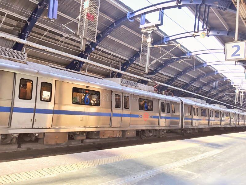 Treno della metropolitana di Delhi ad una stazione della metropolitana più di meno ammucchiata a Nuova Delhi nel tempo di mezzogi fotografie stock