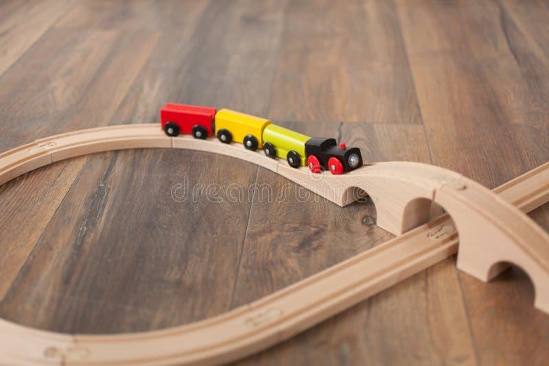 Treno di legno del giocattolo sulla ferrovia con il ponte di legno Pulisca il pavimento laminato immagini stock libere da diritti