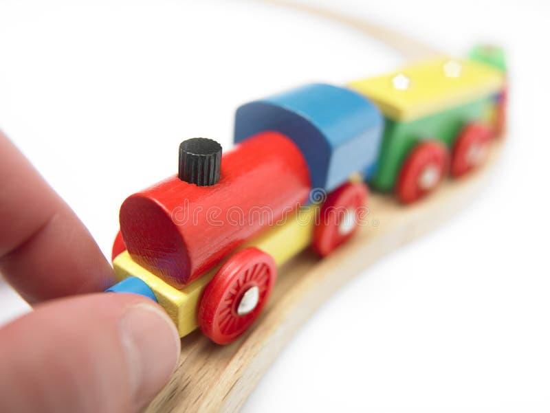 Treno di legno variopinto del giocattolo con la mano isolata su bianco fotografie stock libere da diritti