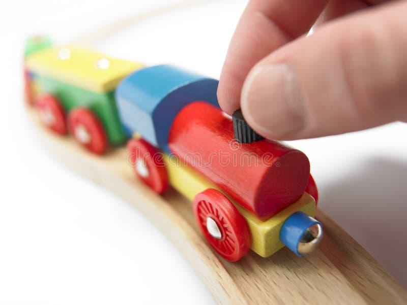 Treno di legno variopinto del giocattolo con la mano isolata su bianco immagini stock