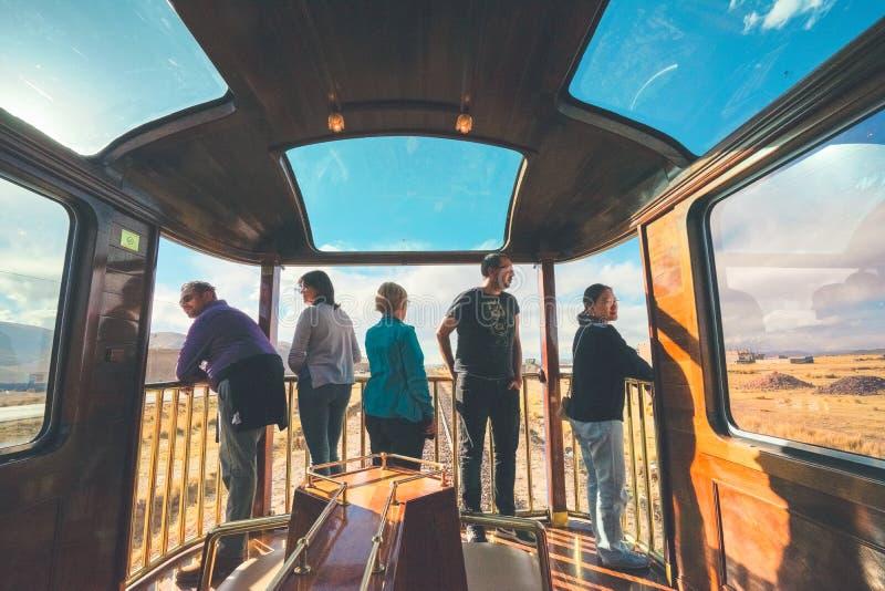 Treno di Titicaca, Perù - 15 agosto 2018: Cinque turisti dai paesi differenti stanno all'aperto l'automobile di osservazione di P immagini stock