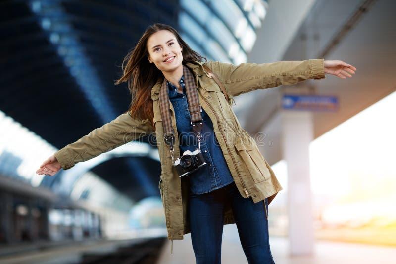 Treno felice del waitng della giovane donna sul binario della stazione ferroviaria immagine stock libera da diritti
