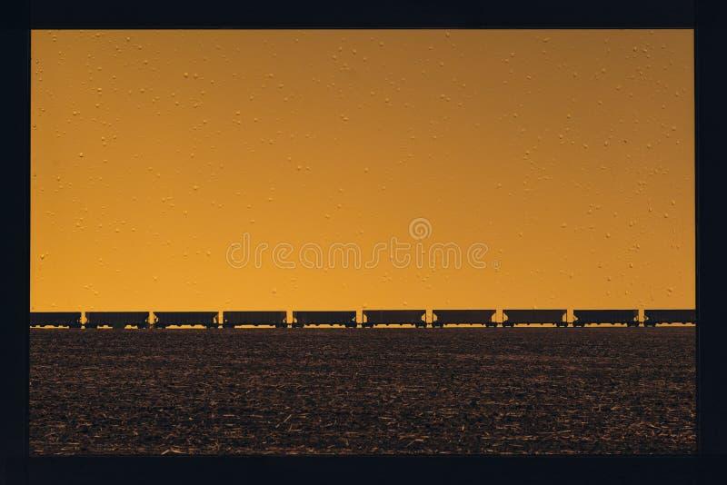 Treno merci che passa sopra sull'orizzonte del campo nella campagna americana attraverso una finestra con le gocce di pioggia immagini stock