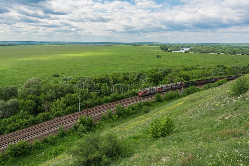 Treno merci con le locomotive che passano dalla ferrovia in Russia, lungo il paesaggio russo tipico, vista superiore fotografia stock