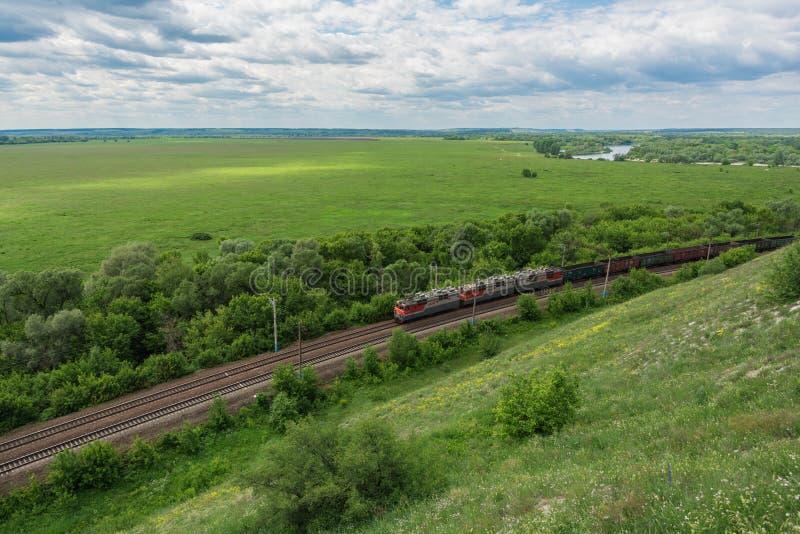 Treno merci con le locomotive che passano dalla ferrovia in Russia, lungo il paesaggio russo tipico, vista superiore immagini stock