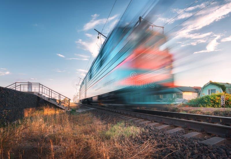 Treno passeggeri ad alta velocità nel moto sulla ferrovia al tramonto fotografie stock libere da diritti