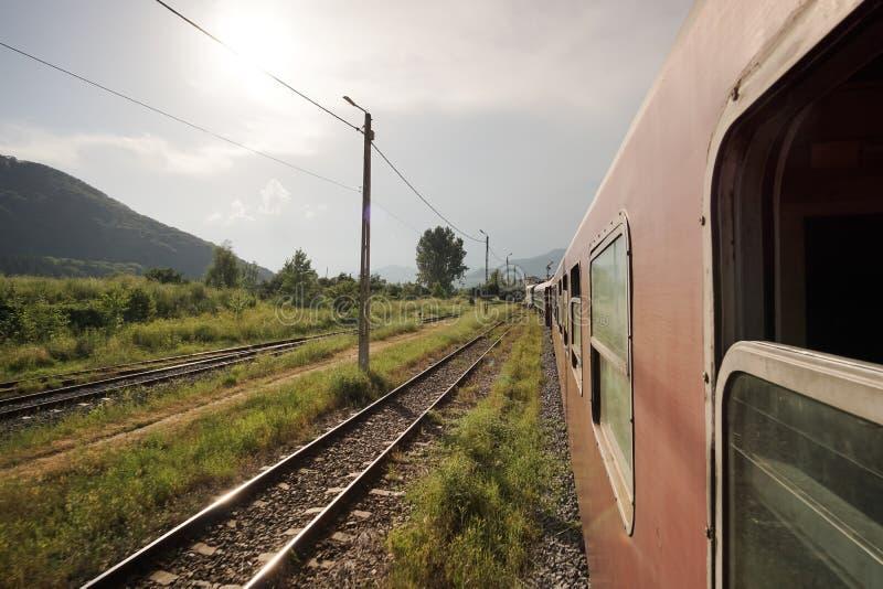 Treno pendolare ferroviario del trasportatore del vecchio stato rumeno di CFR che lascia stazione fotografia stock libera da diritti