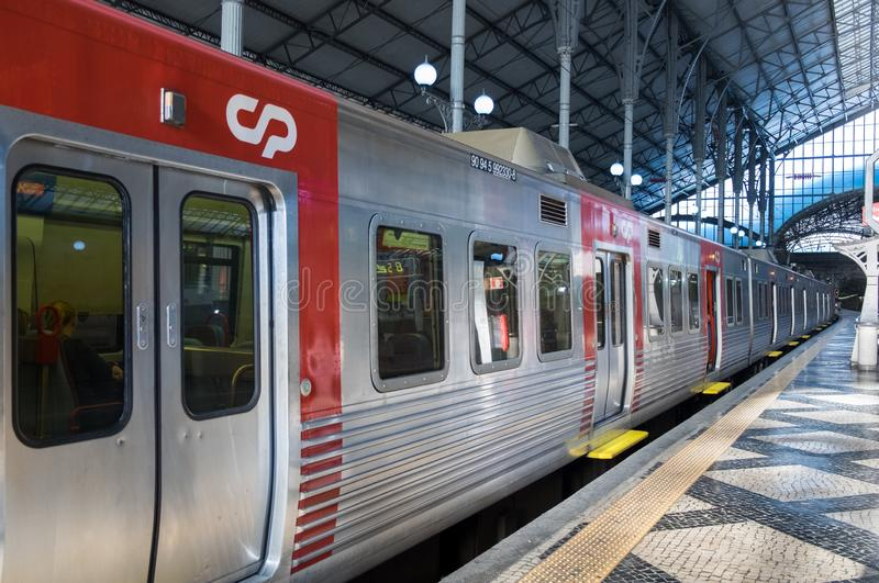 Treno rosso locale alla stazione ferroviaria di Rossio lisbona portugal immagine stock