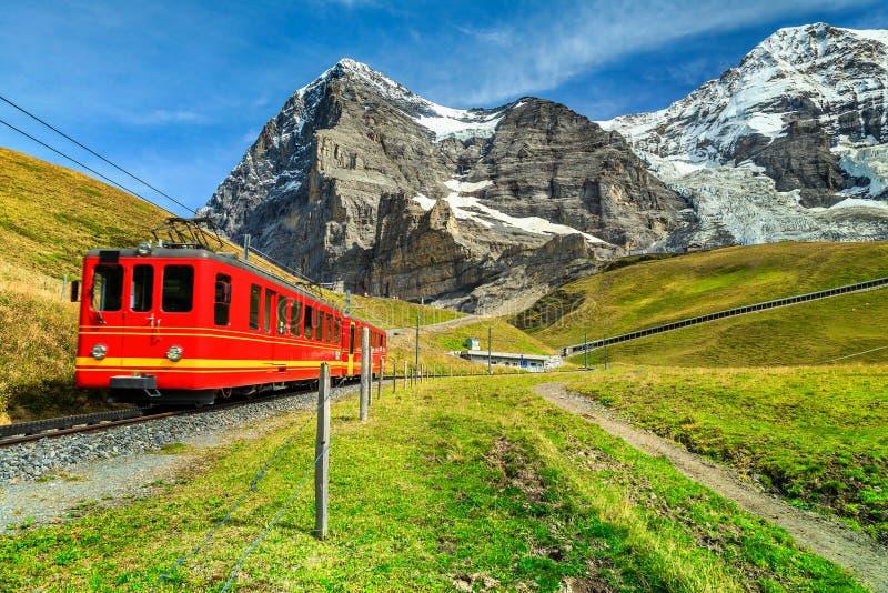 Treno turistico elettrico e fronte del nord di Eiger, Bernese Oberland, Svizzera immagini stock libere da diritti