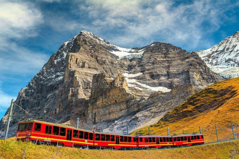 Treno turistico elettrico e picco famoso di Eiger, Bernese Oberland, Svizzera fotografia stock