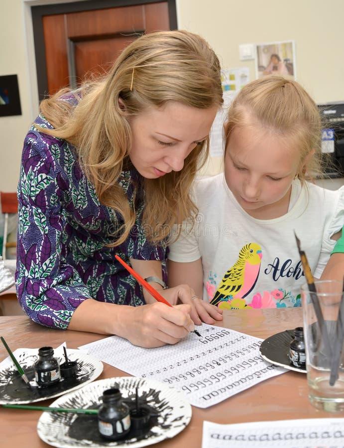 Trenować w pisać listu calligraphical handwriting Zajęcie kaligrafia w dzieciach pracownianych zdjęcia royalty free