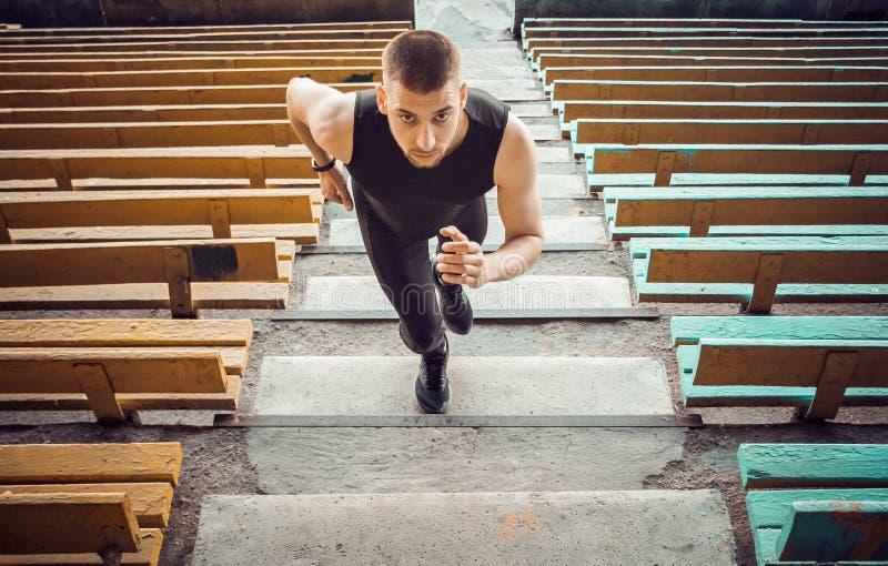 Trens caucasianos do homem na corrida nas escadas Corredor do atletismo no treinamento uniforme do esporte exterior atleta, vista fotos de stock