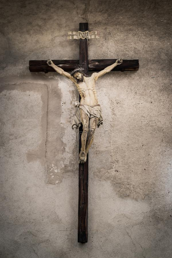 Wooden crucifix hung on the wall of an old church. Trento, Italy - December 25, 2016: Wooden crucifix hung on the wall of an old church royalty free stock photo