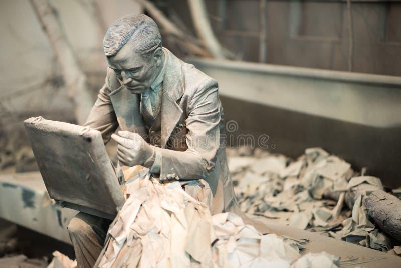 TRENTON, NJ - 17 DE JUNHO DE 2017: Homem de negócio que senta-se para baixo com o breifcase nas terras para a escultura fotografia de stock