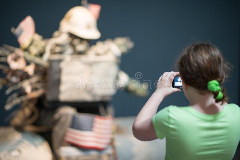 TRENTON, NJ - 17 DE JUNIO DE 2017: Muchacha que toma una imagen con su cámara del objeto expuesto del arte en los argumentos para imagen de archivo