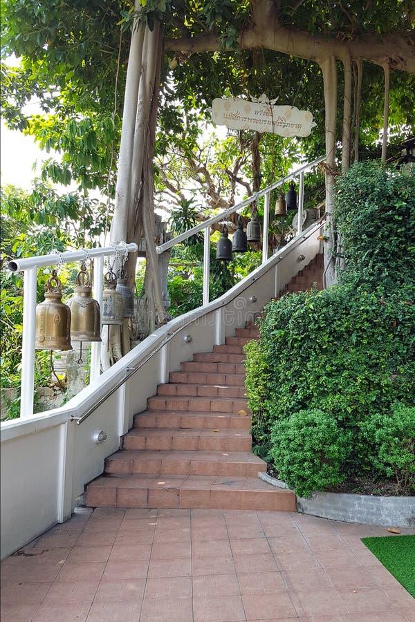 Treppenhaus mit weißen Geländern, auf denen heiliger buddhistischer Glockenfall stockbild