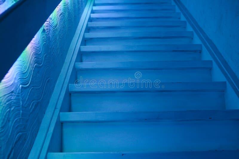 Treppenhaus in verdunkeltem düsterem Blaulicht stockbild