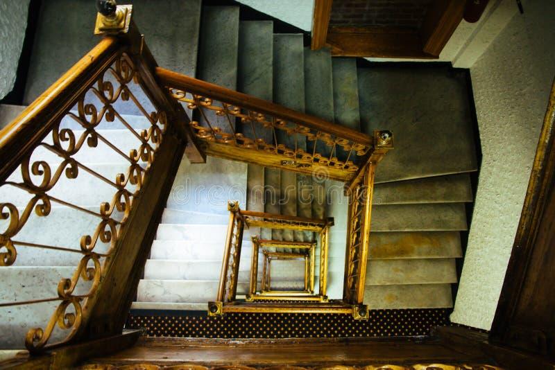 Treppenhaustreppenhaus Alte Weinlese quadratisches Spiralenmultiflug-Treppentreppenhaus mit braunen Holz- und Metallhandläufen stockbild
