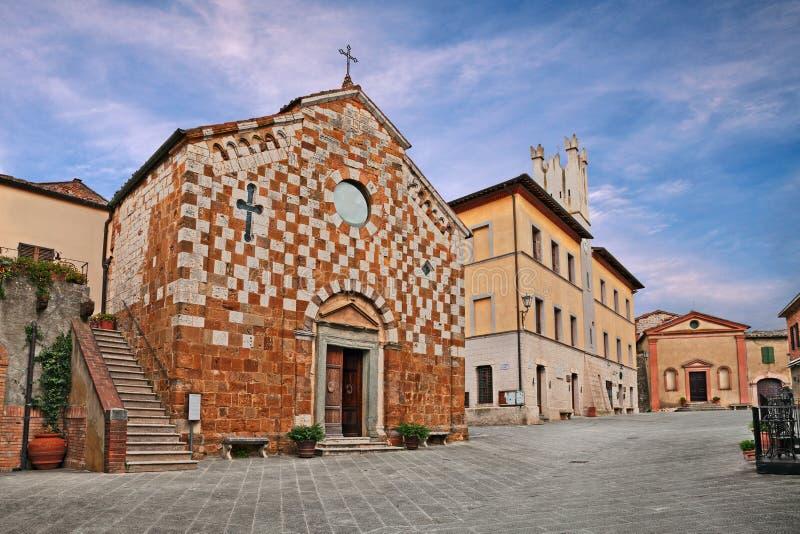 Trequanda, Σιένα, Τοσκάνη, Ιταλία: το κύριο τετράγωνο με τη μεσαιωνική εκκλησία στοκ φωτογραφίες