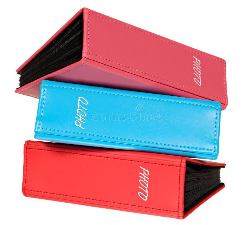 Tres álbumes de fotografía de rosa, de rojo y de azul imagen de archivo