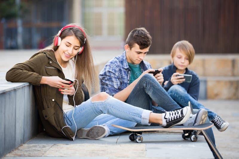 Tres adolescentes con smartphones adentro al aire libre fotos de archivo