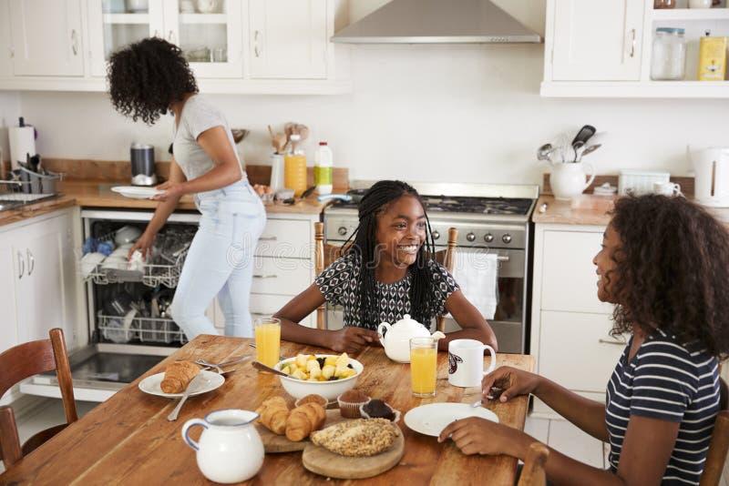 Tres adolescentes que despejan la tabla después de desayuno de la familia foto de archivo libre de regalías