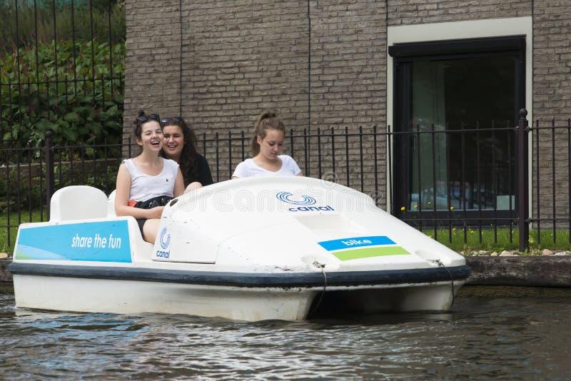 Tres adolescentes que se divierten en un barco del pedal imagen de archivo libre de regalías