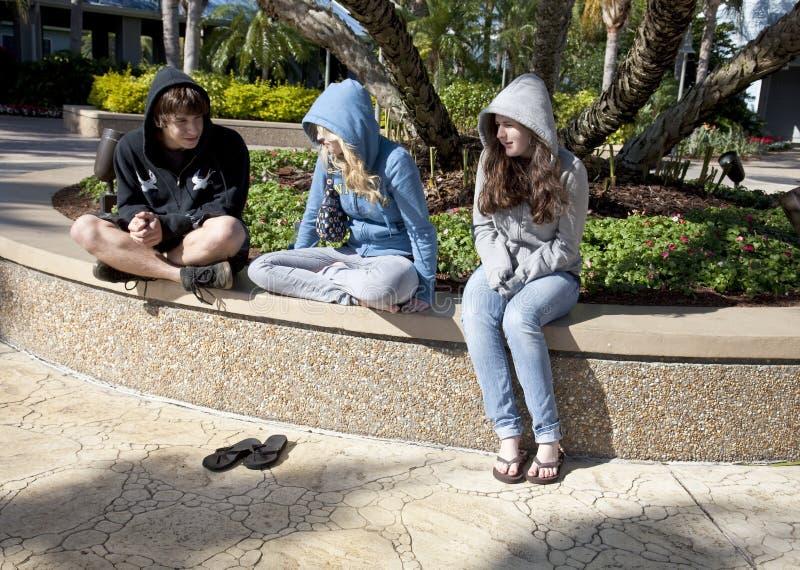 Tres adolescentes que se sientan y que hablan foto de archivo libre de regalías