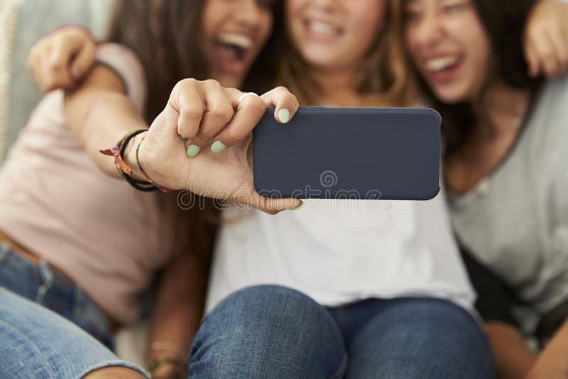 Tres adolescentes que toman el selfie en casa, foco en el teléfono imagenes de archivo