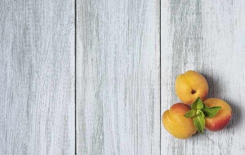 Tres albaricoques frescos dulces en la opinión superior rústica de la tabla vacía de madera imagenes de archivo