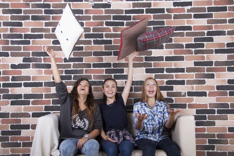 Tres almohadas que lanzan del partido de las muchachas en casa para arriba imagen de archivo libre de regalías
