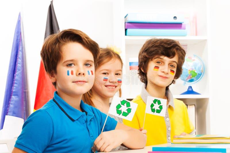 Tres alumnos que se sientan en clase en la lección de la ecología imagen de archivo