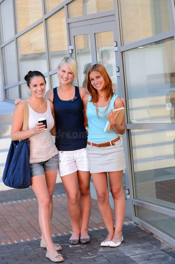 Tres amigas del estudiante fuera de la sonrisa de la universidad imagen de archivo libre de regalías