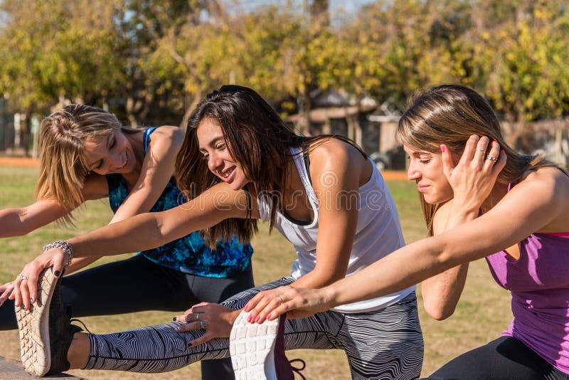 Tres amigas jóvenes trabajando en el parque, al aire libre. Concepto de deporte, salud y estilo de vida fotos de archivo libres de regalías