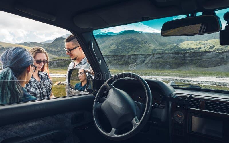 Tres amigos cerca del coche discuten la ruta en el viaje Concepto de las vacaciones del viaje imagen de archivo libre de regalías