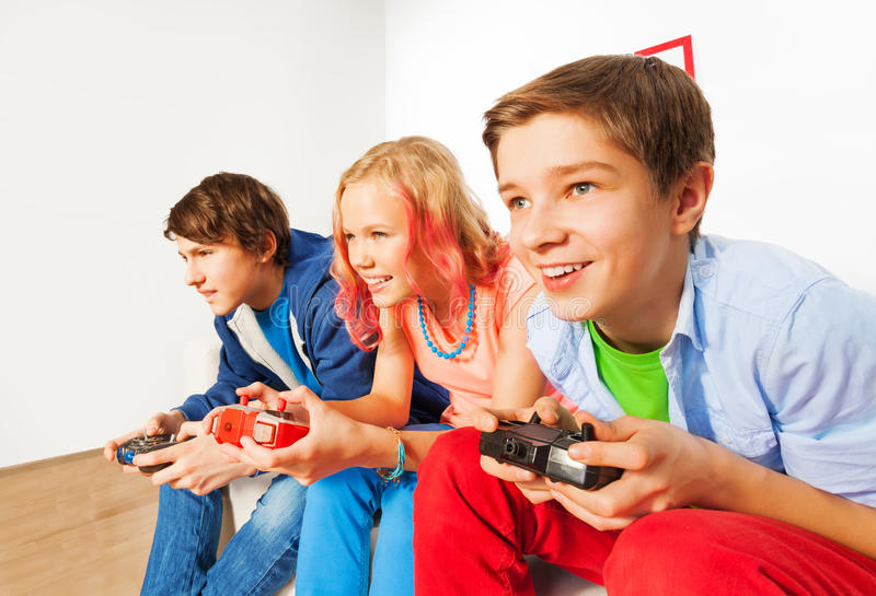 Tres amigos con las palancas de mando que juegan la videoconsola imágenes de archivo libres de regalías