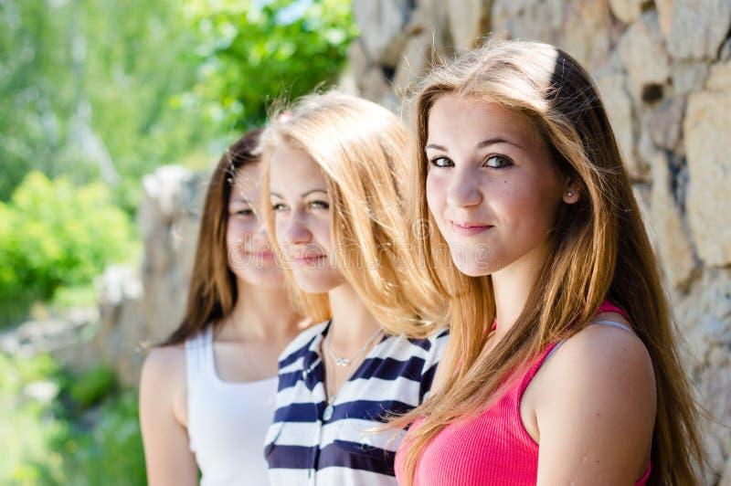 Tres amigos de adolescente felices que sonríen en el fondo de la pared de piedra el día de verano fotos de archivo libres de regalías