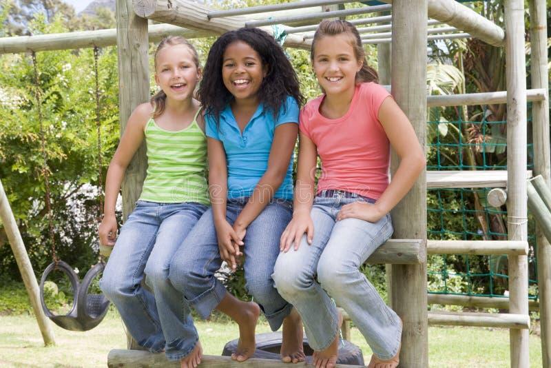 Tres amigos de la chica joven en una sonrisa del patio fotos de archivo