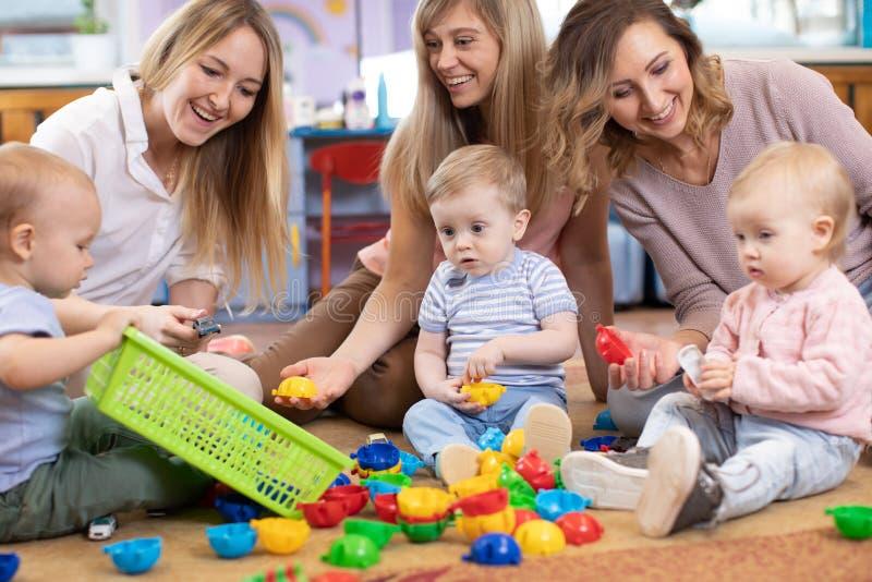 Tres amigos de la mujer con los niños que juegan en el piso en salón imagen de archivo