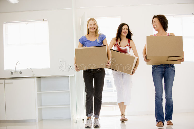Tres amigos de muchacha que se trasladan a la nueva sonrisa casera imagen de archivo libre de regalías