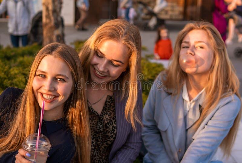 Tres amigos de muchachas que se divierten el la tarde broadway Comiendo el helado, el batido y la masticaci?n de leche fresco de  fotografía de archivo