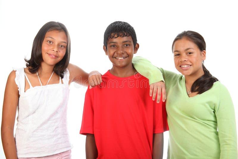 Tres amigos del adolescente en muchacho del estudio y dos muchachas imagen de archivo