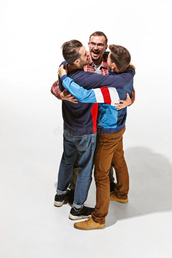 Tres amigos en el desgaste colorido casual que se une y que ríe foto de archivo libre de regalías