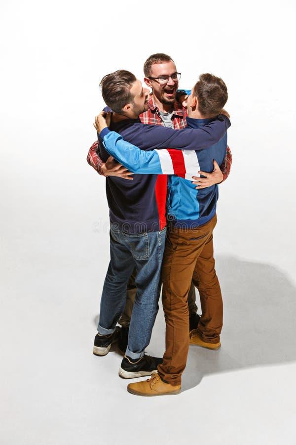 Tres amigos en el desgaste colorido casual que se une y que ríe imágenes de archivo libres de regalías