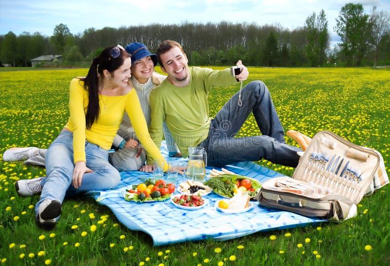 Tres amigos en la comida campestre imagen de archivo libre de regalías