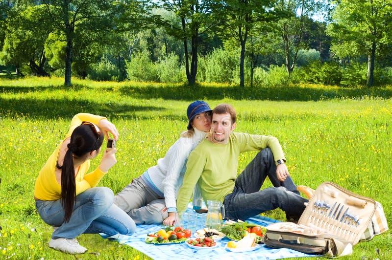 Tres amigos en la comida campestre haciendo las fotos fotografía de archivo